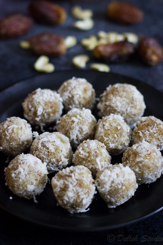 plate full of refined sugar free coconut date balls with coconut and dates at the back