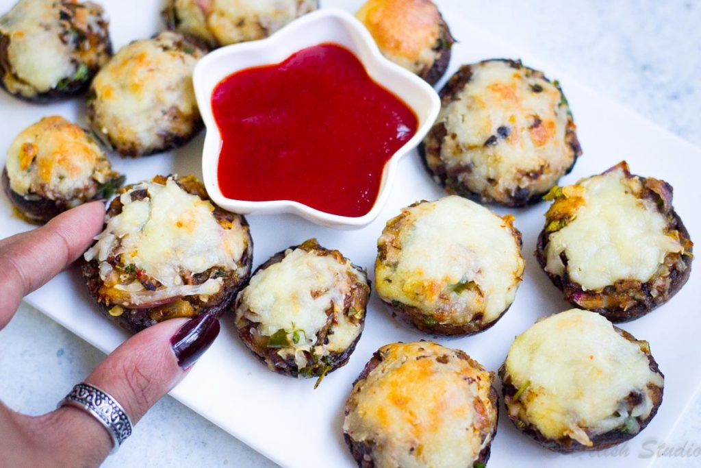 A bite of cheese stuffed mushroom as a party appetiser