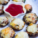 Baked cheese stuffed mushrooms served as vegetarian appetiser.